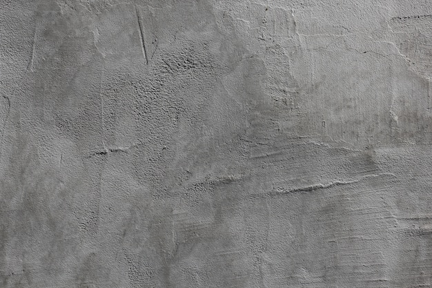 Gray cement mortar on the wall is uneven with streaks.
