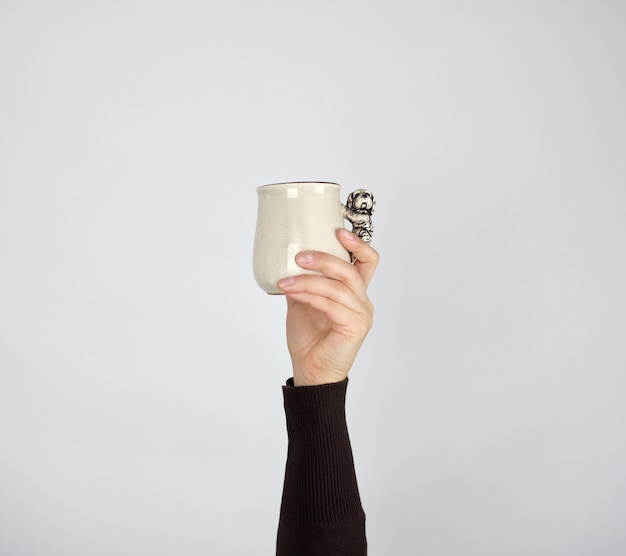 Gray ceramic cup in female hand on a white background, hand raised up