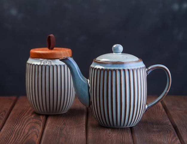Серый керамический чайник на деревянном столе