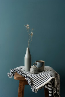 Gray ceramic vase with a mug on a wooden stool by a forest green wall