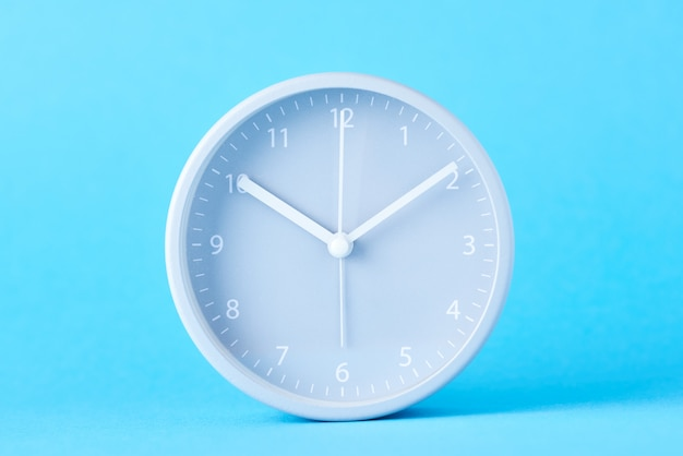 Gray classic alarm clock on a pastel blue background, close up