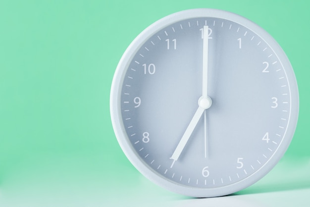 Gray classic alarm clock on a pastel green with copy space