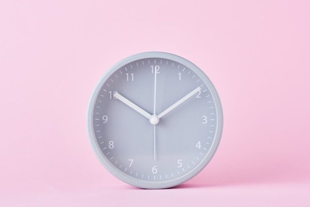 Gray classic alarm clock on a pastel pink background, close up