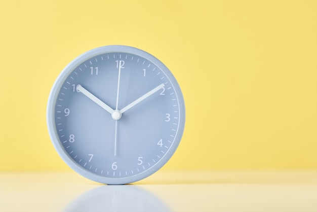 Gray classic alarm clock on a pastel yellow background with copy space