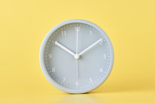 Gray classic alarm clock on a pastel yellow surface, close up