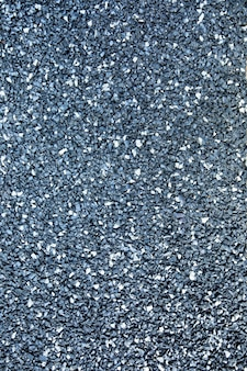 Gray clay crumb, floor covering, sports ground or terrace by the pool, texture, close-up.
