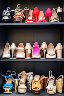 Gray closet shelves full of fashion female shoes on heels pair storage organization of cupboard