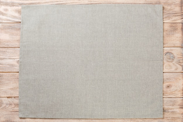 Gray cloth napkin on brown rustic wood, top view with copy space