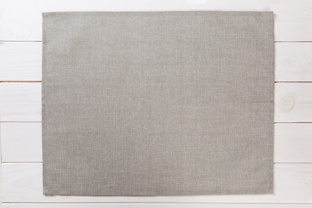 Gray cloth napkin on white rustic wooden background top view with copy space.