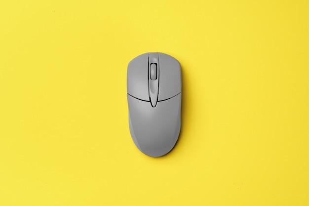 Серая компьютерная мышь на желтом