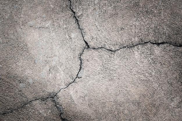 灰色のコンクリートの背景。道路上の古いアスファルトのひび割れ
