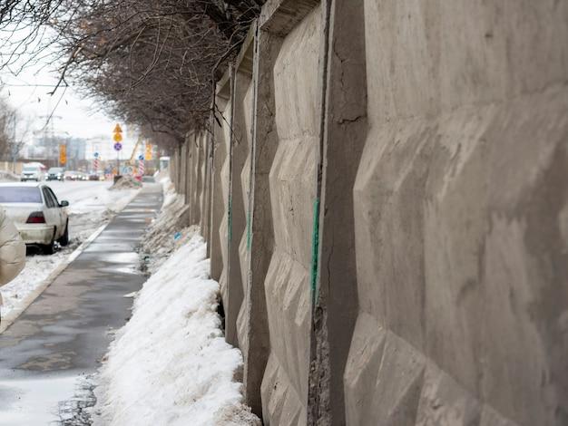 다이아몬드 모양의 회색 콘크리트 울타리. 도로, 울타리를 따라 볼 수 있습니다. 러시아 울타리