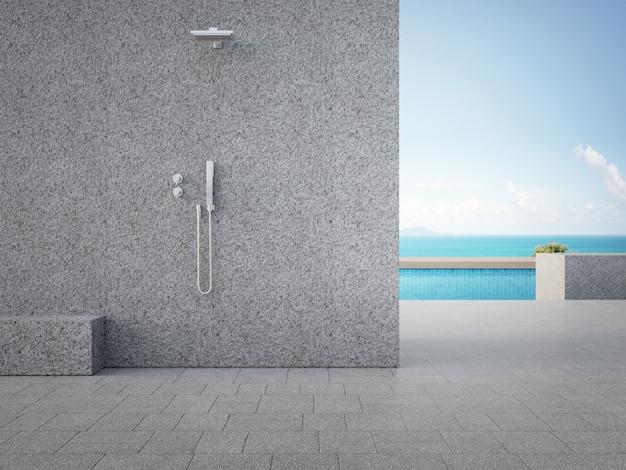 Серая бетонная стена с душем на открытом воздухе