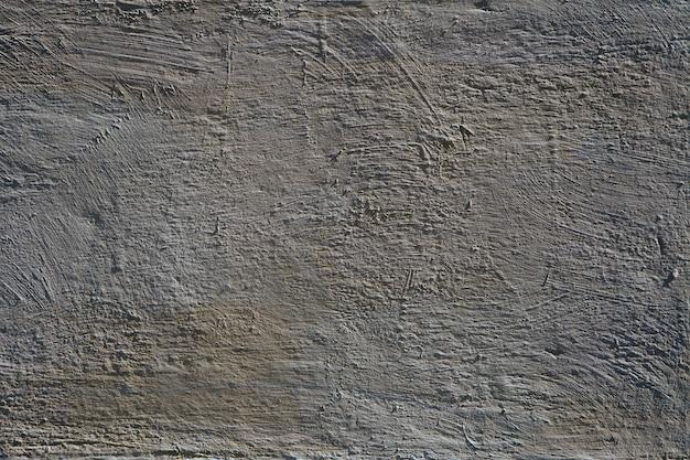 灰色のコンクリートの壁、小さなテクスチャの詳細を持つセメントの背景ペイントの黄色のビンテージスタイル。古いテクスチャ表面