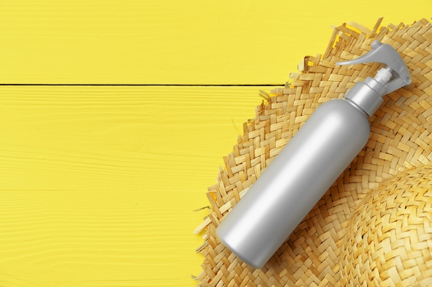 Gray cosmetic bottle on yellow wooden background top view