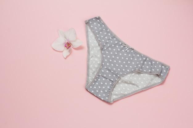분홍색 배경에 난초 꽃이 있는 회색 면 팬티. 여성 속옷 세트입니다. 평면도.