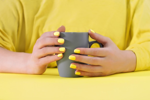 Gray cup in hands with yellow manicure on yellow table. colors of the year 2021. illuminating and ultimate gray.