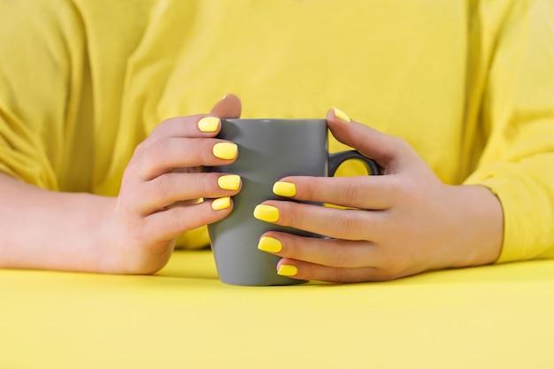 黄色のテーブルに黄色のマニキュアと手に灰色のカップ。 2021年の色。イルミネーションとアルティメットグレー。