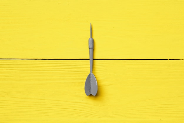 Gray dart arrow on yellow background copy space top view
