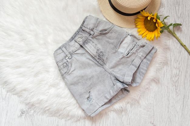 Gray denim shorts, sunflower and hat on white fur