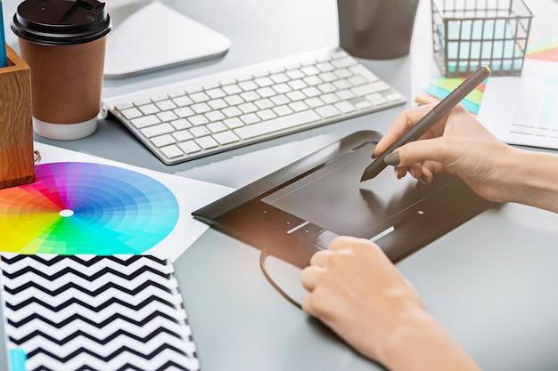 Scrivania grigia con laptop, blocco note con foglio bianco, vaso di fiori, stilo e tablet per ritocco