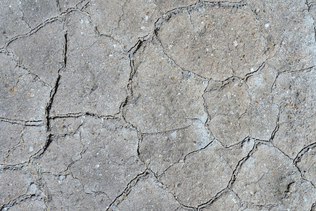 Gray dry cracked surface of volcanic ground turned into desert. natural pattern texture or background taken in environment in crater of active volcano. concept: drought soil erosion, global warming.