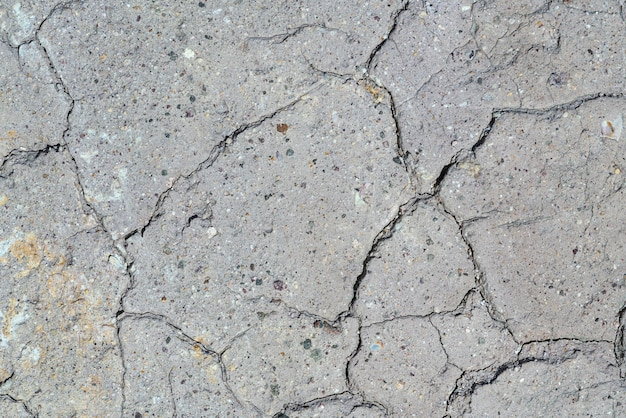 Gray dry cracked surface of volcanic soil turned into desert. natural background or texture taken in environment in crater of active volcano. concept: global warming, drought soil erosion.