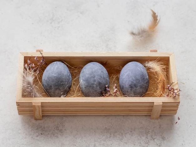 Серые пасхальные яйца в деревянной коробке на белой поверхности. пасхальные яйца окрашены в чайный отвар каркаде. копировать пространство.