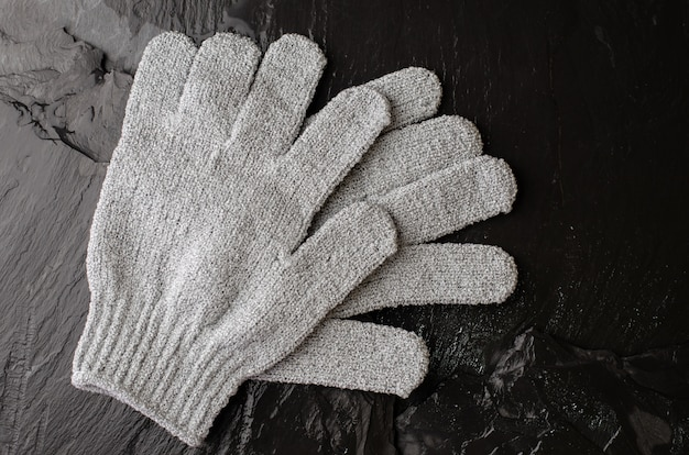Gray exfoliating gloves for shower use on black stone background