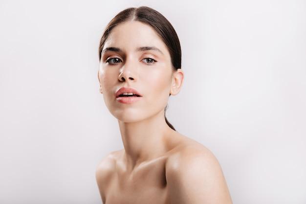 흰 벽에 감각적으로 포즈를 취하는 건강한 피부와 검은 머리를 가진 회색 눈의 여성 모델.