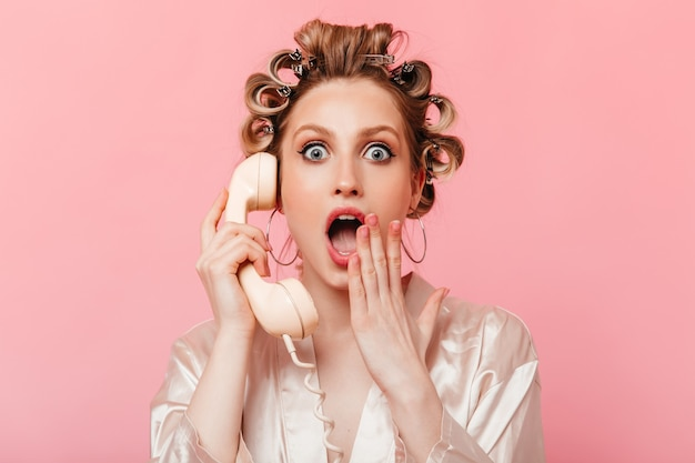 Casalinga dagli occhi grigi in veste che copre la bocca dalla sorpresa e parla al telefono