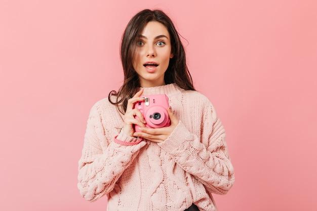Una signora dagli occhi grigi con un'espressione stupita fa una foto su una mini fotocamera rosa. donna con capelli scuri dritti in maglione lavorato a maglia in posa su uno sfondo isolato.
