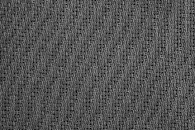 Gray fabric close-up. weaving of individual threads. knitted polyester. low pile synthetic fiber.