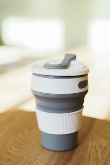 Gray foldable silicone cup for drinks without plastic in the style of zero waste on a interior room, close-up.