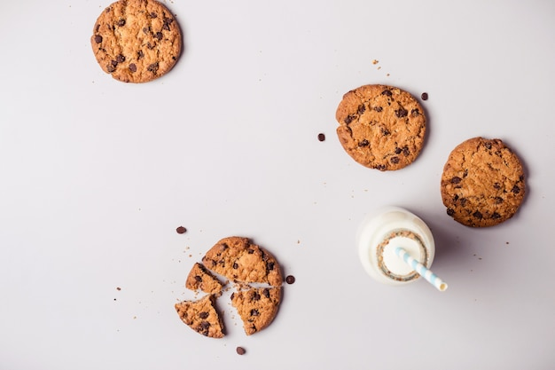 Gray food background with chocolate chip cookies and bottle of milk.