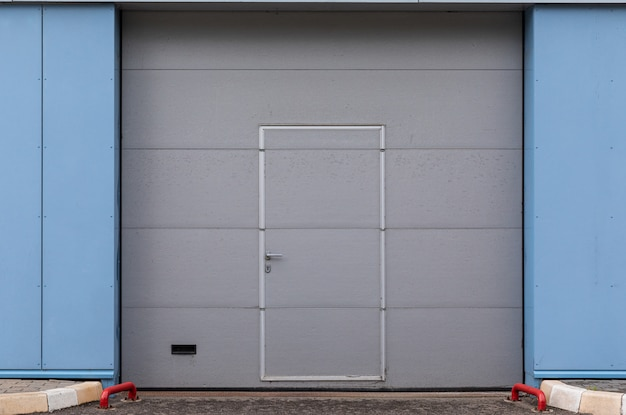 Gray gate door with built-in small door on blue paneled wall