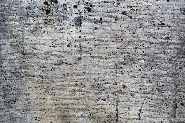 Gray grunge texture of old damaged roofing paper with spots.