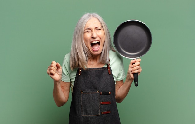 鍋と白髪かなり中年シェフの女性
