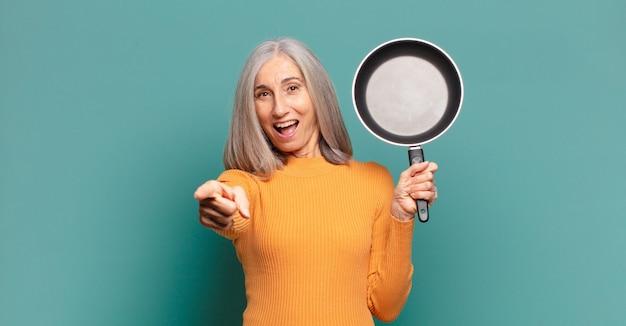 Седые волосы довольно женщина среднего возраста учится готовить со сковородой