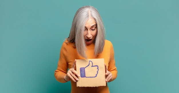 バナーのようなソーシャルメディアを保持している白髪のきれいな女性