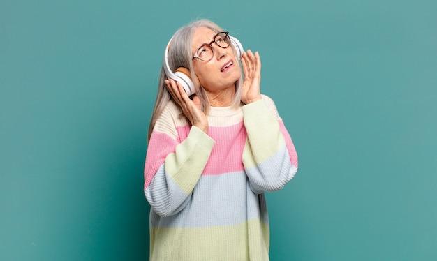 彼女のヘッドフォンで音楽を聞いている白髪のきれいな女性