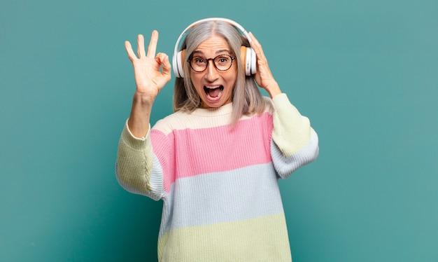 회색 머리 예쁜여자가 그녀의 헤드폰으로 듣는 음악