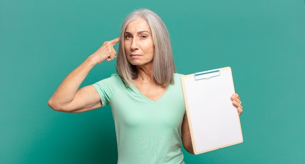 Седые волосы симпатичная женщина показывает пустой лист бумаги
