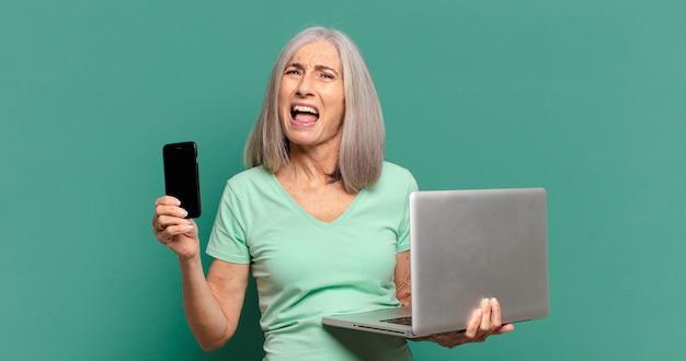 セルとラップトップを持つ白髪のきれいな女性