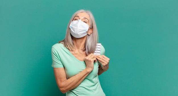 保護マスクと丸薬を持つ白髪のきれいな女性