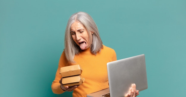 Gray hair pretty woman with a laptop. take away fast food concept