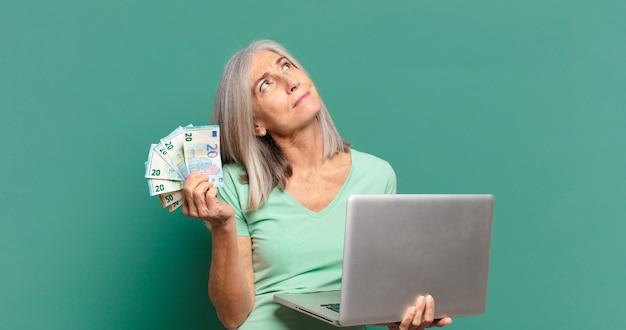 Седые волосы красивая женщина с деньгами и ноутбуком