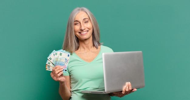 お金とラップトップを持つ白髪のきれいな女性