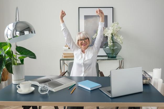 Седые волосы женщина в белой блузке счастлива в офисе