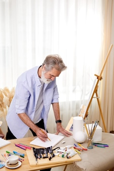 Gray haired artist concentrated on work looking down at sheet, holding pencil in hands